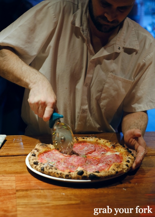 Cutting sopressa and honey woodfired sourdough pizza at Dimitri's Pizzeria on Oxford Street in Darlinghurst Sydney
