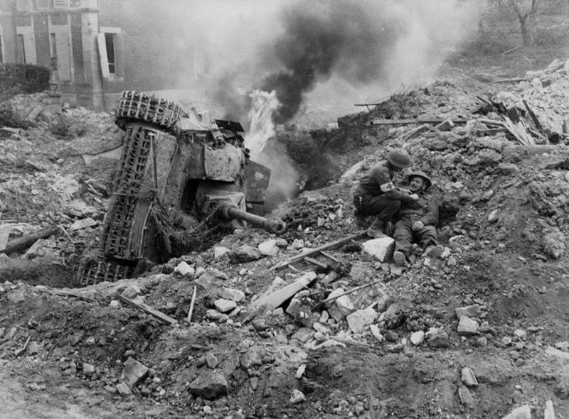 Чиновник-капитан: солдату Содружества оказывается помощь возле горящей StuG III, в Falaise Pocket, Франция. Август 1944