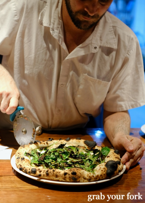 Cutting fluffy blistered woodfired sourdough pizza at Dimitri's Pizzeria on Oxford Street in Darlinghurst Sydney
