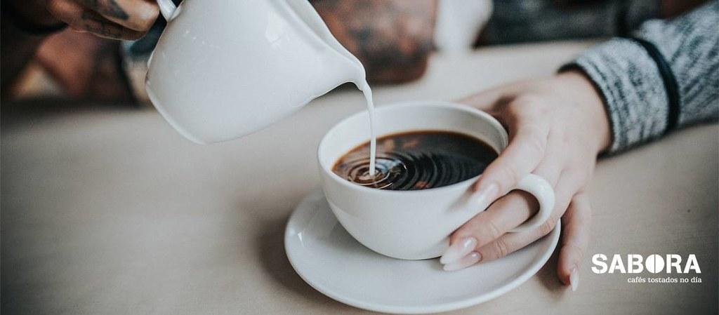 Botando leite no café.