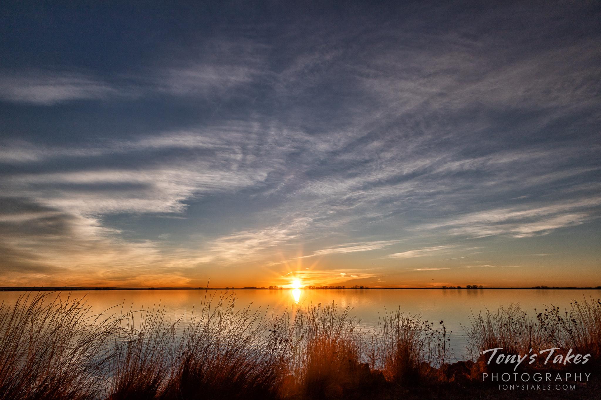 The sun bursts over the horizon at Jackson Lake State Park, Colorado. (© Tony's Takes)
