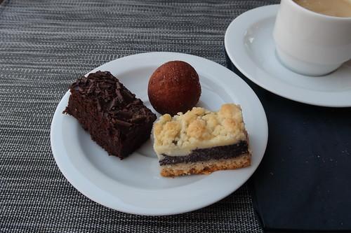 Stückchen von Mohnkuchen und Schokoladenkuchen sowie Hefeteigbällchen zu weiterer Tasse Kaffee