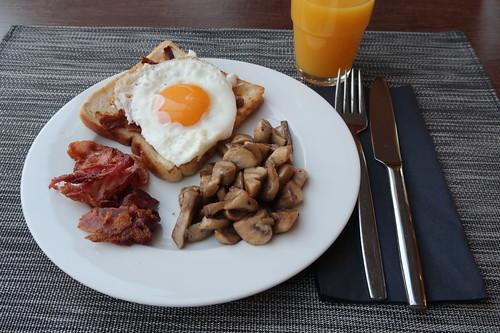 Orangensaft zu gebratenem Toast mit Spiegelei, Bacon und Champignons
