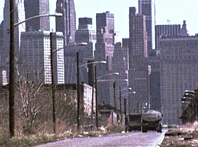Low resolution wasteland looking down Johnston Avenue by the abandoned Central Railroad of New Jersey terminal on the left. The towers of Lower Manhattan hover across the Hudson as if in an utterly different world. Jersey City. April 1976