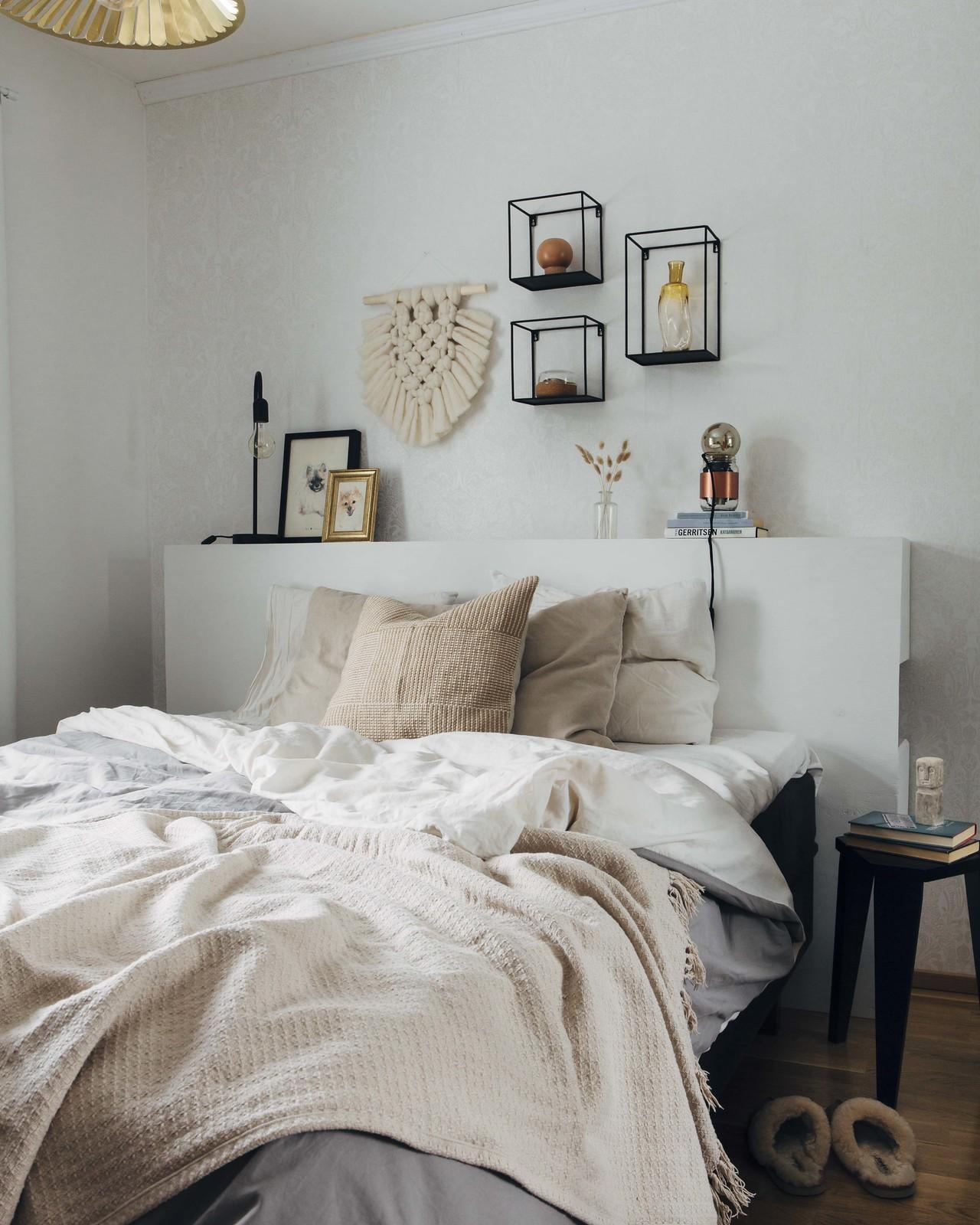 Vaalea makuuhuone, jossa on sänky, jonka päällä on oljensävyinen torkkupeitto.