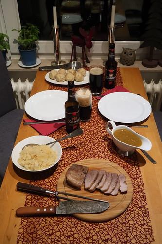 Schweinebraten mit Schwarzbiersoße, Semmelknödeln und Sauerkraut (Tischbild)