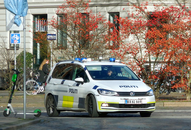 Copenhagen Police traffic car VW Touran *BX61669 patrols past trees loaded with toxic berries