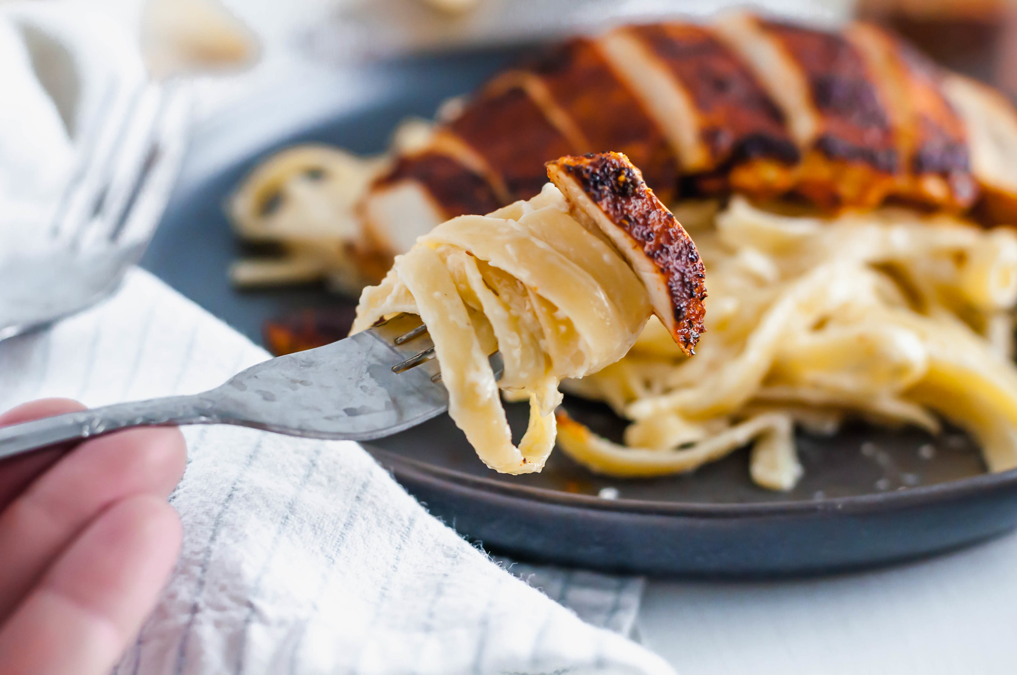 This Blackened Chicken Alfredo is the ultimate weeknight meal. Done in 30 minutes and packed with flavor. Easy enough for any weeknight but fancy enough for guests too. Homemade blackening seasoning covered tender chicken cutlets served over simple, cheesy homemade fettucine alfredo.