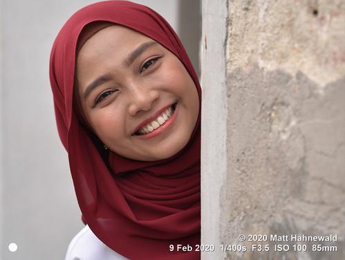 matthahnewaldphotography facingtheworld qualityphoto head tiltedhead face eyes eyebrows teeth expression lookingatcamera headscarf hijab tudung consensual fun conceptual diversity humanity travel tourism lifestyle happiness beauty optimism virtue cultural wall hiding visitor penang malaysia asia asian malay malaysian human person one female young woman women primelens nikond610 nikkorafs85mmf18g 85mm street portrait closeup headshot fullfaceview outdoor naturallight colour posingcamera smiling beautiful pretty lovely cheerful copyspace blank message clarity smilingeyes georgetown muslimah