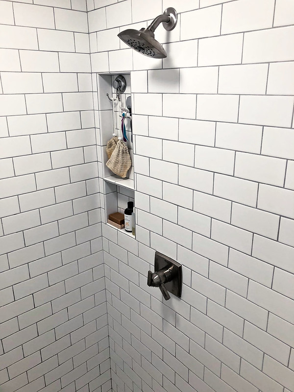 white subway tile shower with builtin niche