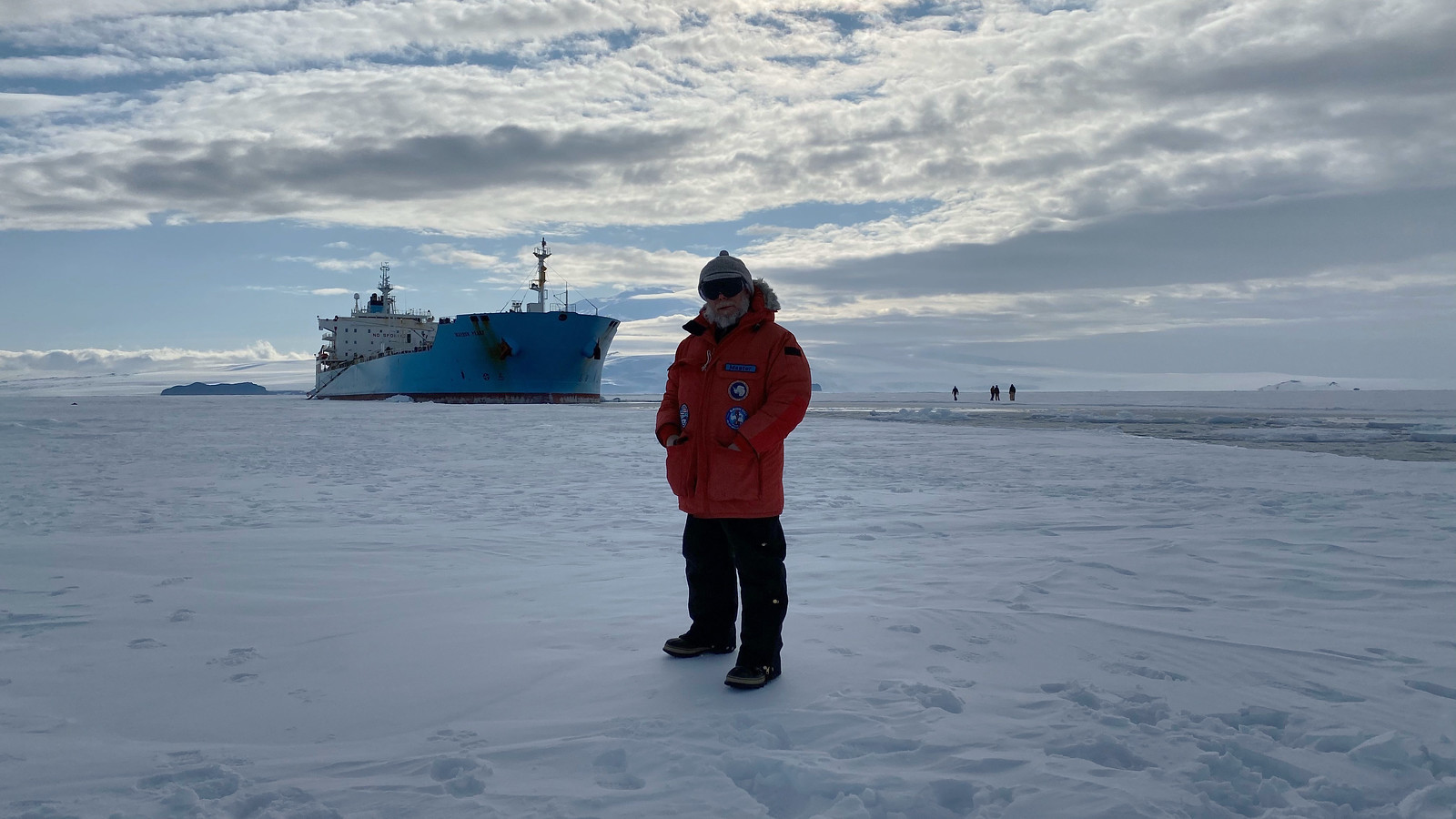 Capt. E.M. Hatton, civilian master of MT Maersk Peary, stands on an patch of Antarctic ice with his ship in the background, Feb. 13. (U.S. Navy)