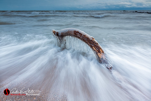 milwaukee wisconsin unitedstatesofamerica atwaterbeach shorewood wi mke sand beach ice frozen freeze tree wood branch buried snow winter cold discoverwisconsin travelwisconsin waves canon sunrise nosun landscape 5dmarkiii longexposure