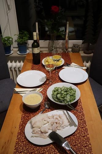 Gedünsteter Fisch mit Senfsoße, Salzkartoffeln und Gurkensalat (Tischbild)