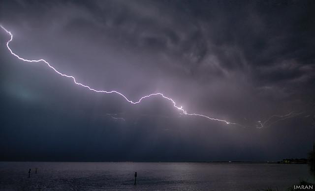Angry Cloud Monster Glares As White Lightning Whiplashes Sky Over Tampa Bay Turning Black Night Blue - IMRAN™
