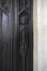south door: a cloaked figure with a rosary (16th Century)