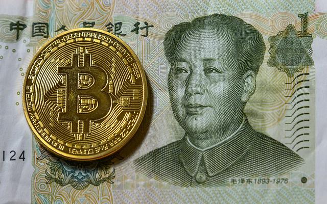 Chinese Renminbi billnote and golden bitcoin