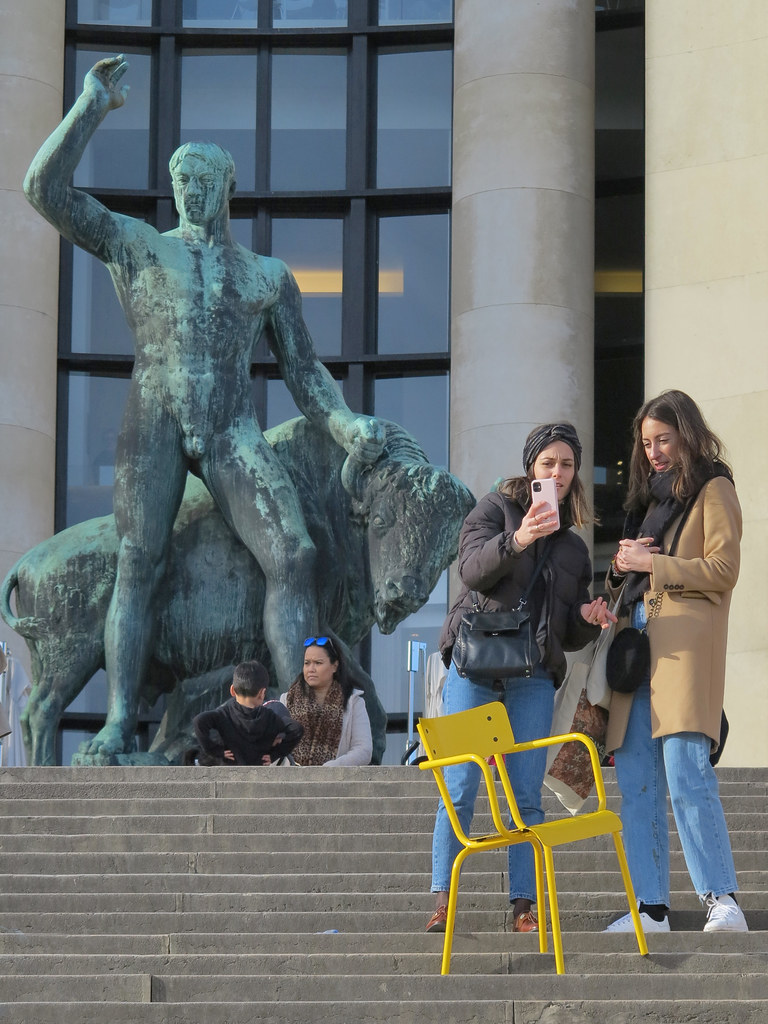 Girl carrying a yellow chair around the city for the sole purpose of taking pictures of it