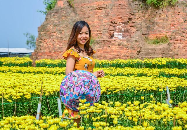 Young Asian woman standing at flower garden