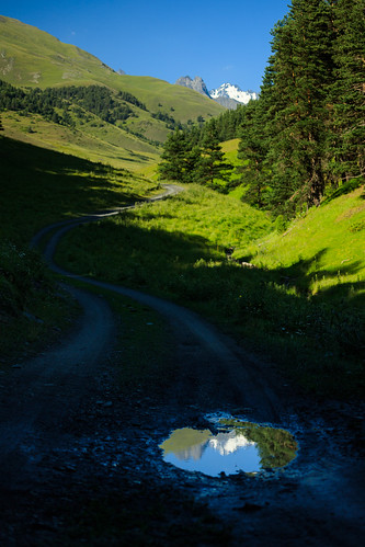 tusheti diklo kakheti georgia hiking trail caucasus mountains reflection puddle snow summit valley road