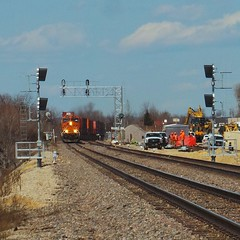 The BNSF forces are in the process of upgrading the signals on the Aurora sub in Desoto, WI as a train approaches.