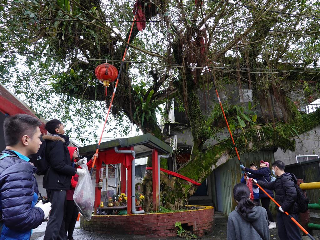 參加淨山的熱心民眾,拿著長桿要把樹上的天燈紙勾下來,框架多已被取走。孫文臨攝