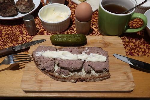 In Scheiben geschnittene Pferdebulette mit Mayonnaise auf Majanne-Brot mit Gewürzgurken