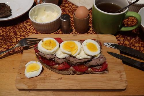 Aufgeschnittene Pferdebulette mit Tomaten, Mayonnaise und hart gekochtem Ei auf Majanne-Brot