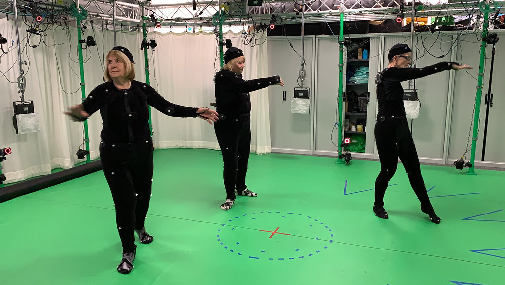 Three mature ladies wearing motion capture suits doing exercises in a motion capture studio