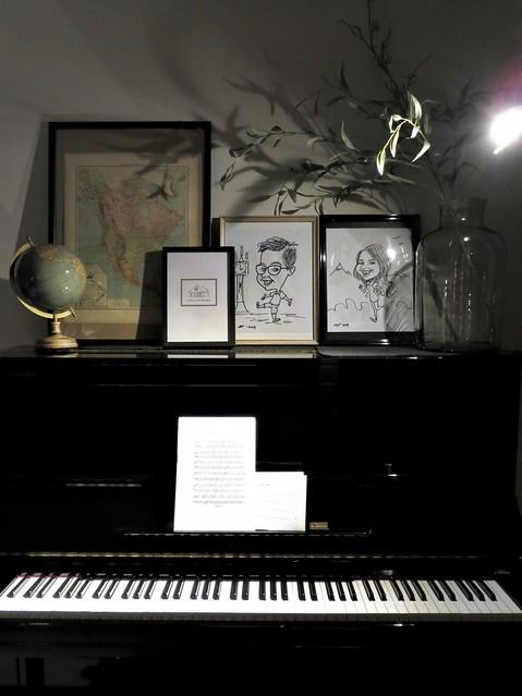 Vaas met takken, globe en foto's op zwarte piano