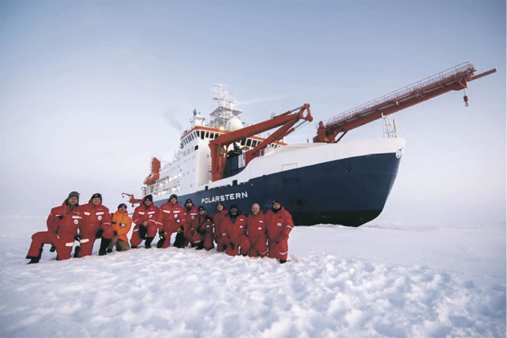 Members of the Atmospheric Radiation Measurement installation team stand in front of the icebreaker R/V Polarstern.