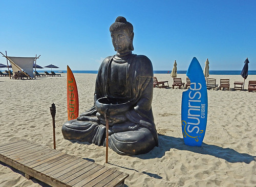 Buddha flanked by shark-bitten surfboards at the beach in Puerto Escondido, Mexico