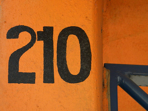 Room number 210 on an orange wall in Huatulco, Mexico