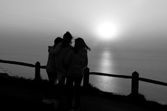 Three girls looking out to sea