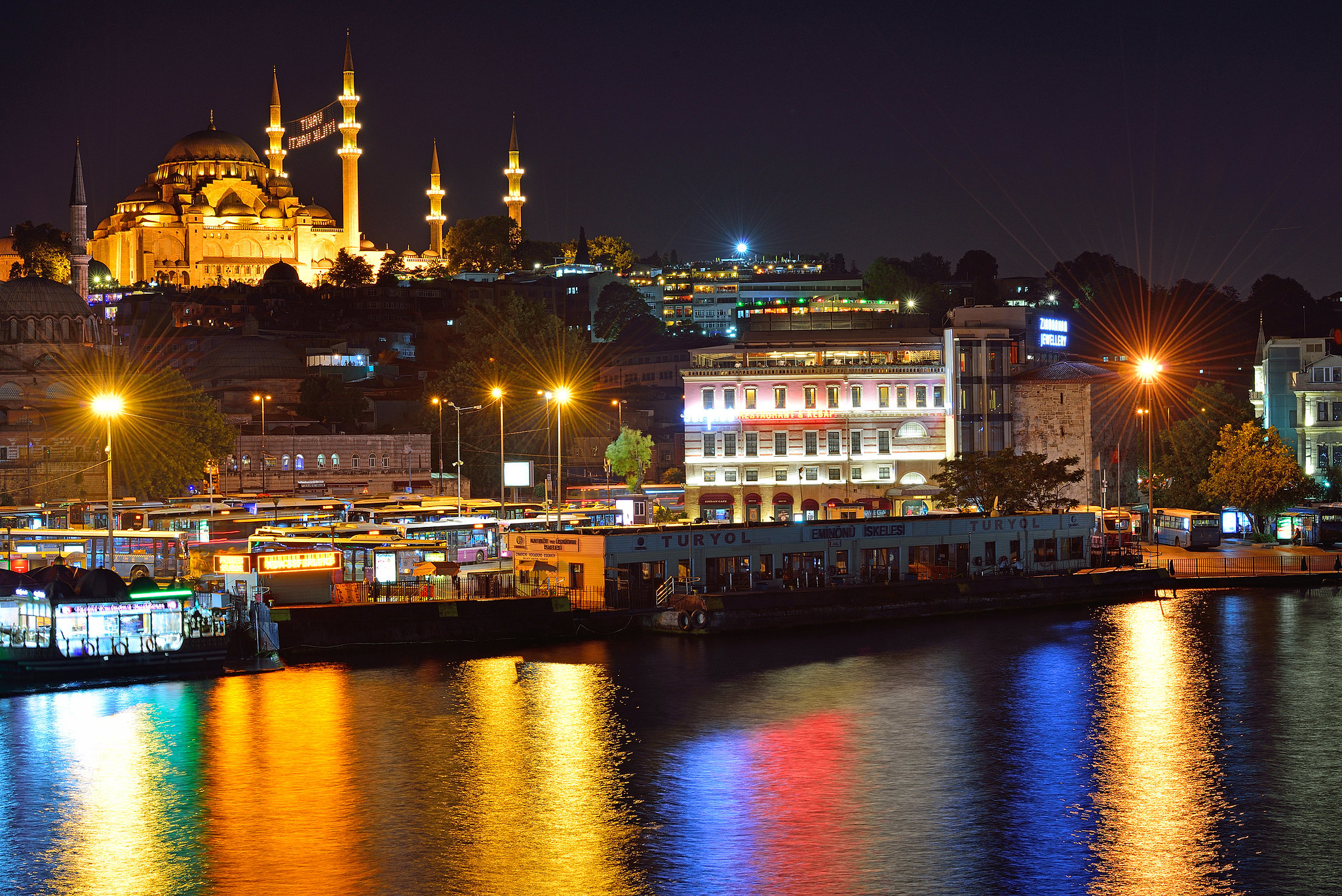 Istanbul at night with Suleymaniye Mosque and beautiful multi-colored reflections in the water of the Golden Horn Bay. View from Galata Bridge.