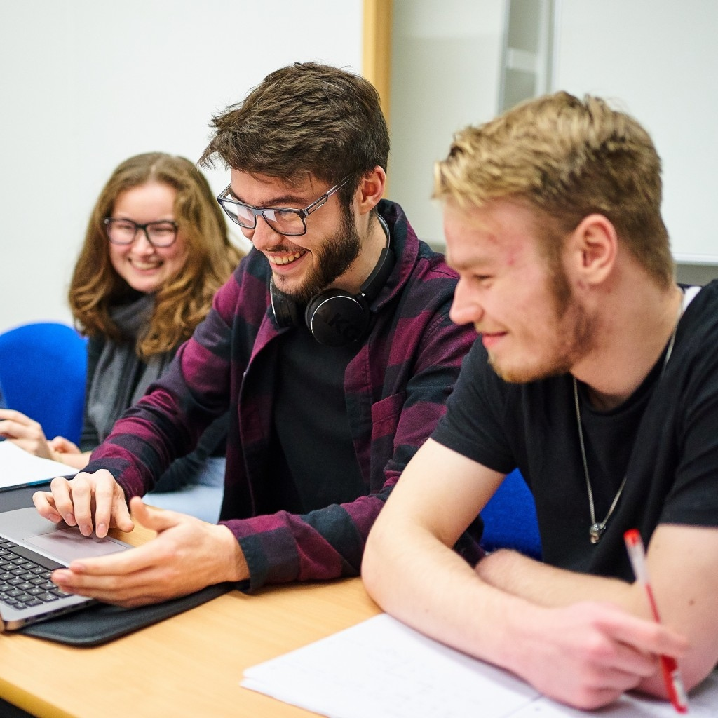 A group of students solving a problem on a laptop