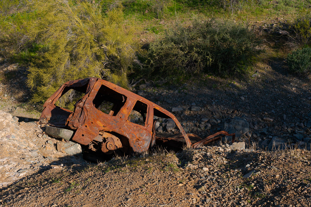 A derelict car perches on the edge of a wash on the Dixie Mountain Loop trail in Phoenix Sonoran Reserve in Phoenix, Arizona in February 2020