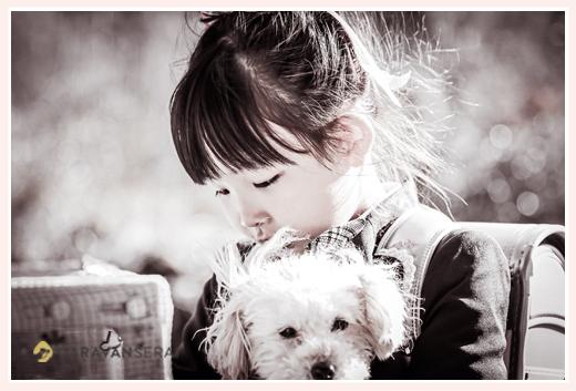 ランドセルを背負い犬を抱っこした女の子 モノクロ写真