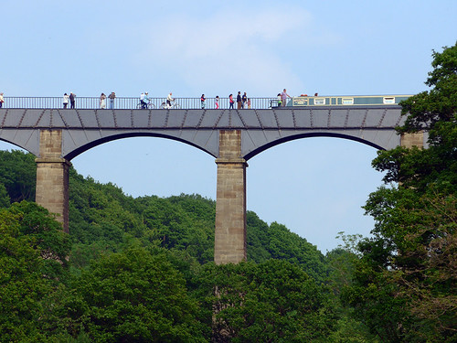 People walking along the canal in the Pontcysylite Aqueduct in Wales