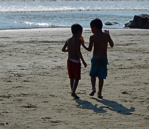 Boys sharing an ice cream cone on the beach in Zihuatanejo, Mexico