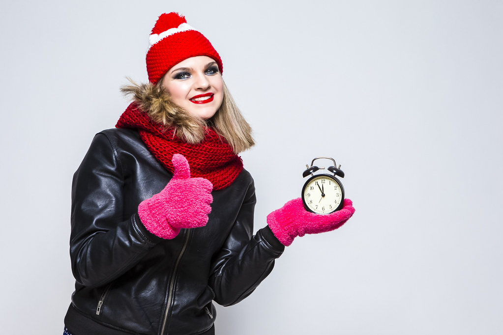 Time Concepts. Portrait of Exclaiming  Caucasian Blond Girl In Warm Hat and Scarf Posing With Thumbs Up Sign With Round Clock And Happy Expression On White
