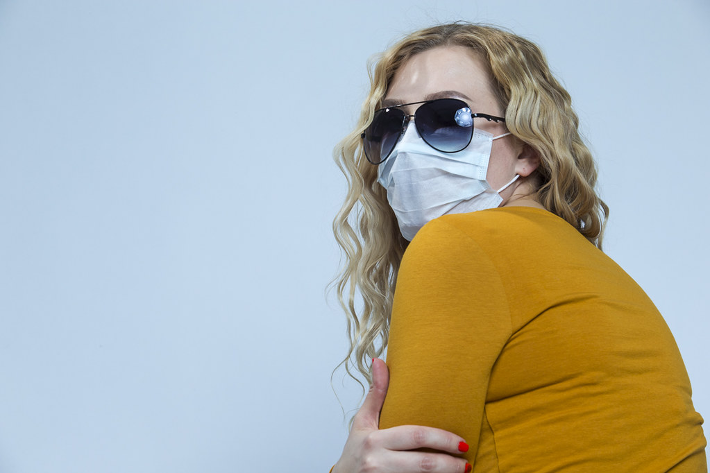 Portrait of Depressed Caucasian Woman Wearing Flu Virus Mask For Viral Prevention With Black Protective Glasses. Against Gray.
