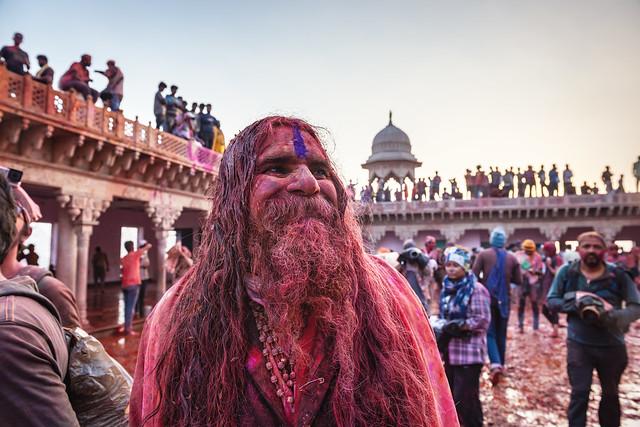 MATHURA, INDIA - Feburary 25,2018: Indian Hindu revellers smeared with colour dance during the Holi festival celebration in Mathura, India