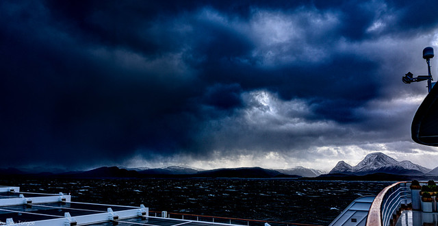 Dark clouds overshadowing sunrise make beautiful photos off coastal mountains of Norway from the deck of Viking Sky cruiseship.