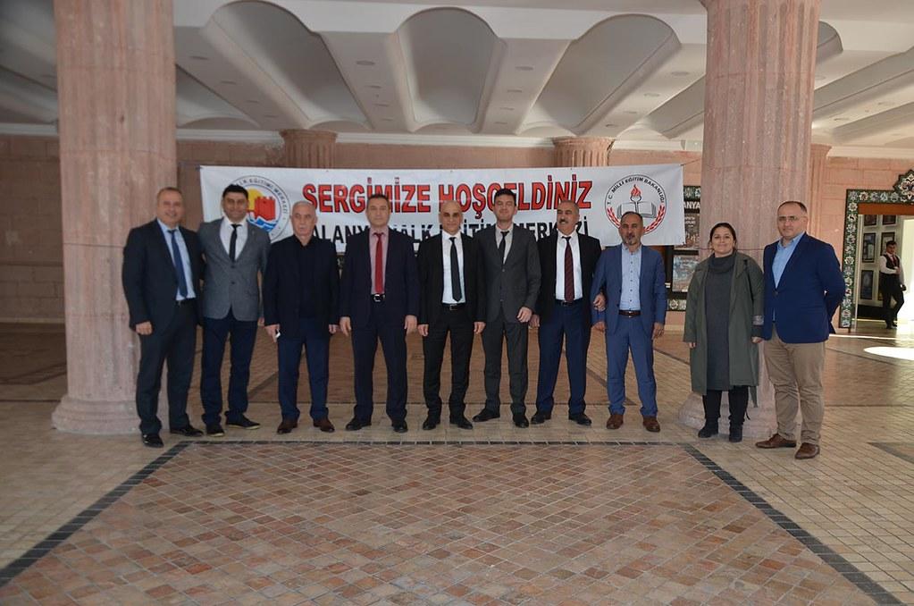 Alanya İlçe Milli Eğitim Müdürü Hüseyin Er ve sergiye gelen misafirlerle Albüm'e poz verdiler.