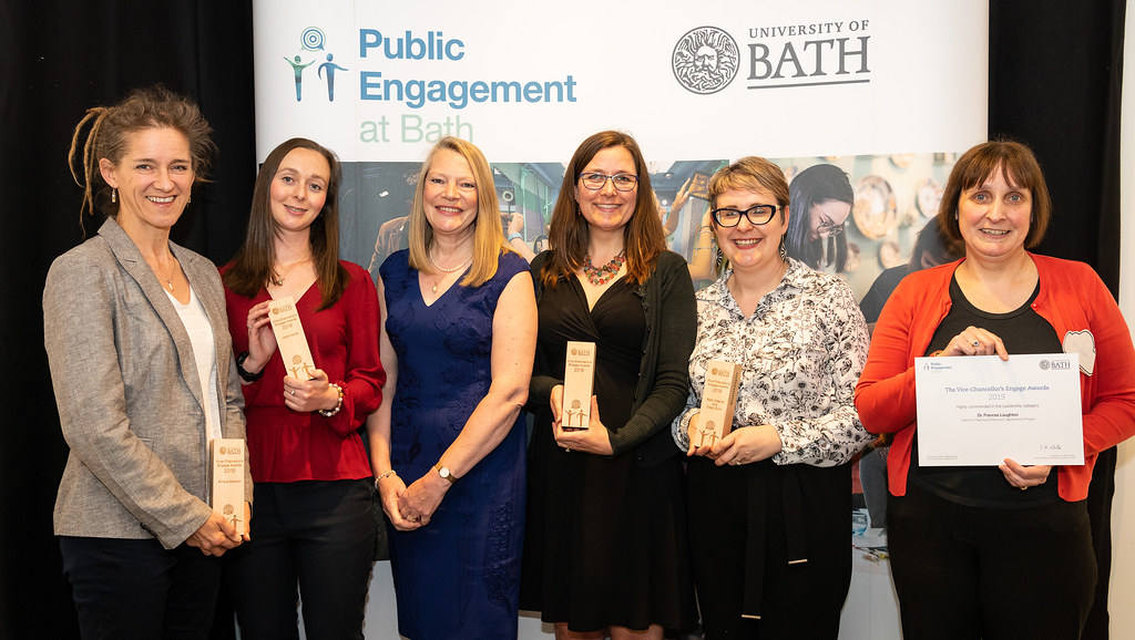 Award winners holding their awards standing in front of a banner that says Public Engagement at Bath