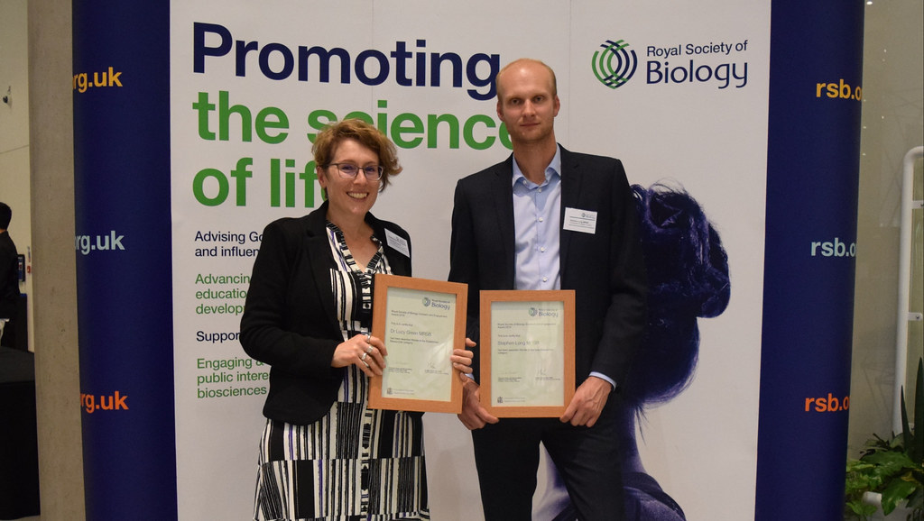 Two award winners holding their awards in front of a Royal Society of Biology banner