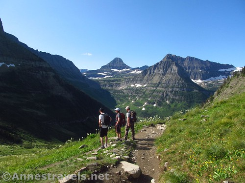 Three hikers pause just below the crest of Haystack Pass to look back at Logan Pass, Highline Trail, Glacier National Park, Montana