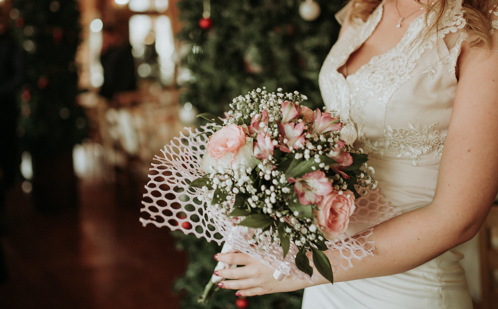 The bride holds a bouquet of flowers in her hand.