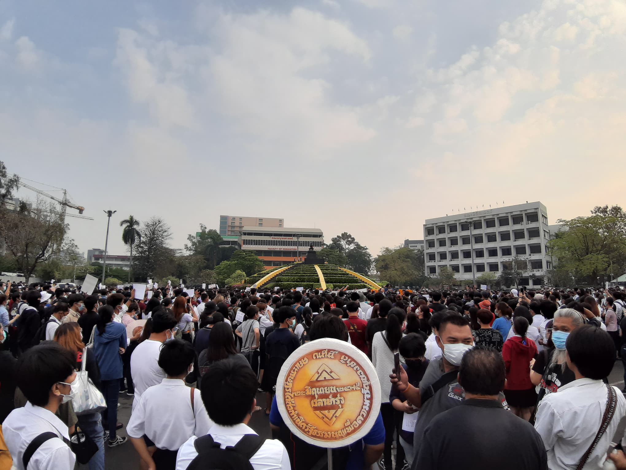 A picture of the demonstration at Ramkhamhaeng University, with one of the protestors carrying a styrofoam model of the missing People's Party Plague about the size of his torso.
