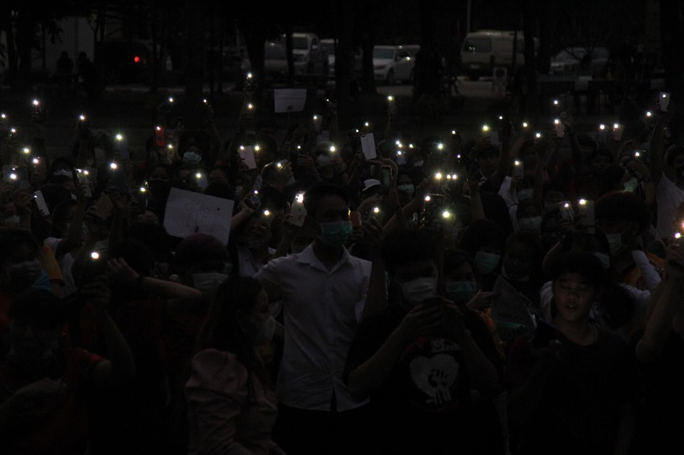 A picture showing the lights from the phones used by the protestors at Thammasat University Lampang with the protestors' shadowy figures in the background.